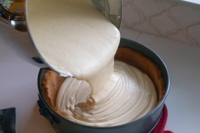 Pouring cheesecake batter into graham crust in springform pan