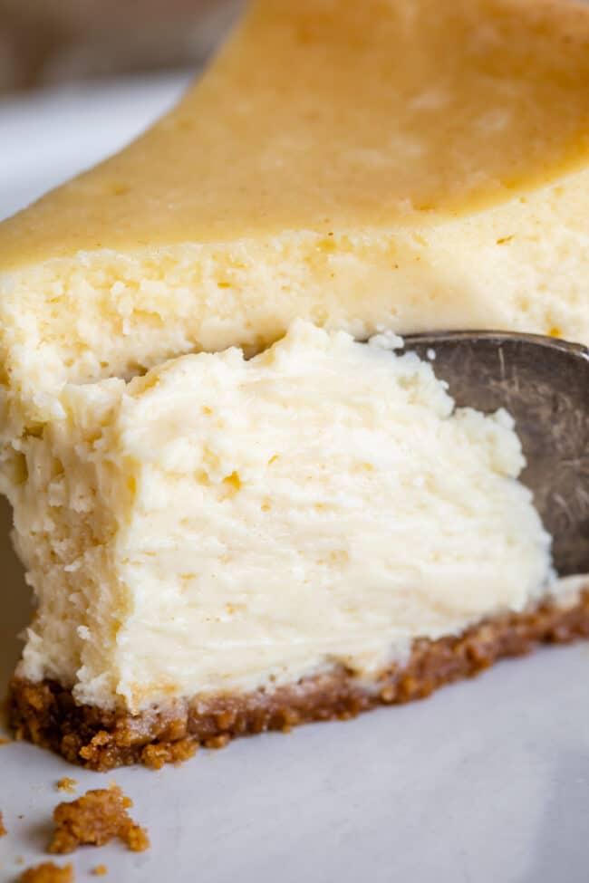 a fork slicing down into a piece of classic cheesecake