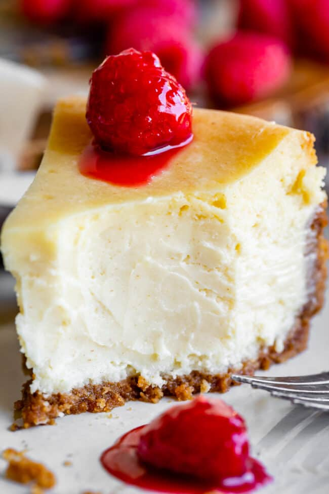 a bite taken out of easy cheesecake with raspberries on top