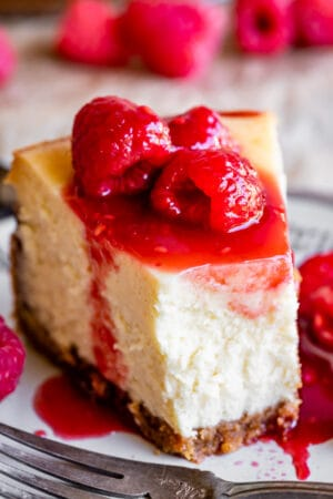classic new york cheesecake with a bite taken out and raspberries