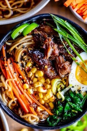 pork ramen in a black bowl with garnishes: carrots, egg, spinach, green onions