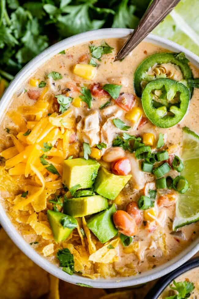 white chicken chili in a bowl on a wooden board with jalapenos