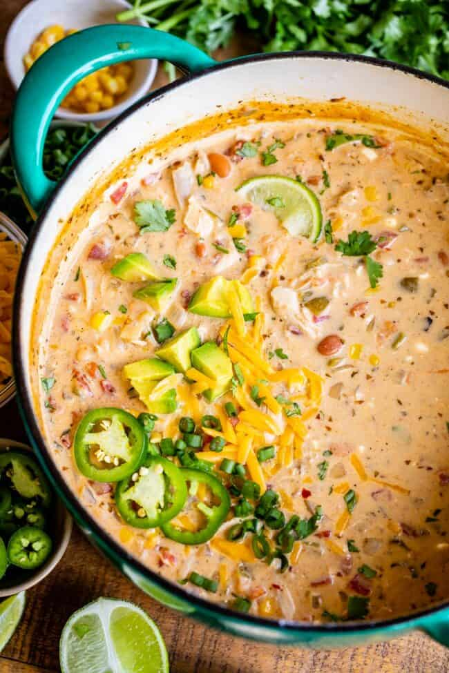 chicken and white bean chili in a pot with jalapeno and cheese garnishes