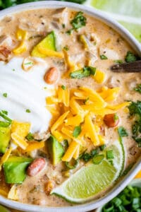 white bean chicken chili in a white bowl with lime and cheese garnish