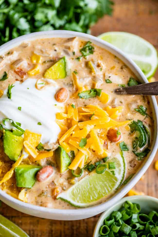 creamy white chicken chili in a large bowl with sour cream and lime and spoon